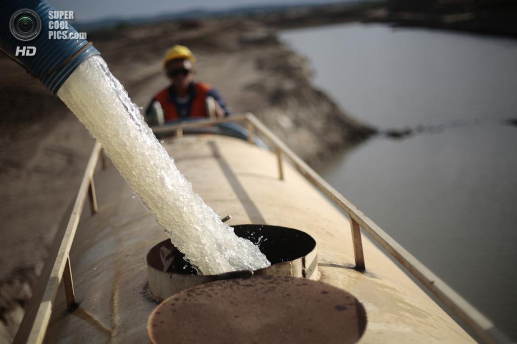Бразилия. Маурити, Сеара. 28 января. Рабочие наполняют контейнер грузовика водой из канала. (REUTERS/Ueslei Marcelino)