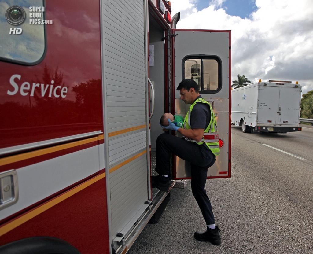 США. Свитуотер, Флорида. 20 февраля. Парамедики увозят Себастьяна в госпиталь. (AP Photo/Al Díaz, Miami Herald)