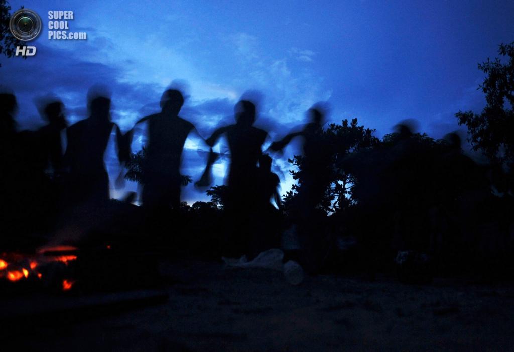 Бразилия. Пара. 24 января. Воины-мундуруку поют и танцуют на закате во время поисков нелегальных золотодобытчиков. (REUTERS/Lunae Parracho)