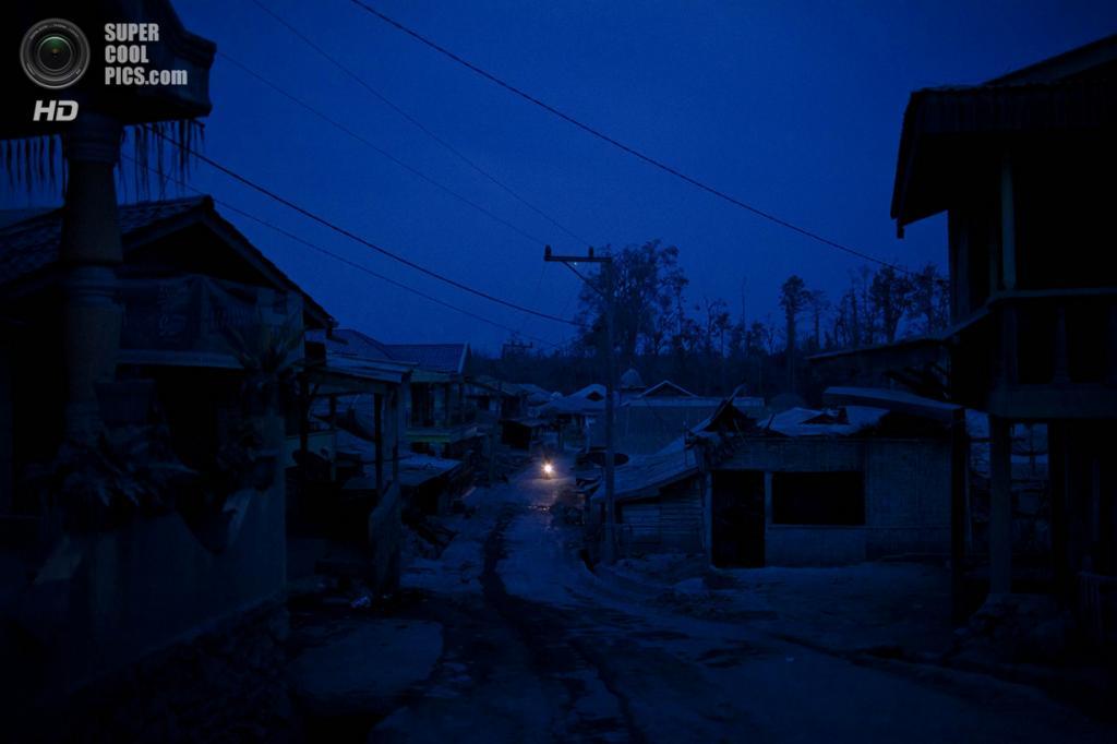 Индонезия. Кута-Райят, Северная Суматра. 12 февраля. Мотоциклист проезжает по заброшенной деревне, покрытой вулканическим пеплом, у вулкана Синабунг. (Ulet Ifansasti/Getty Images)