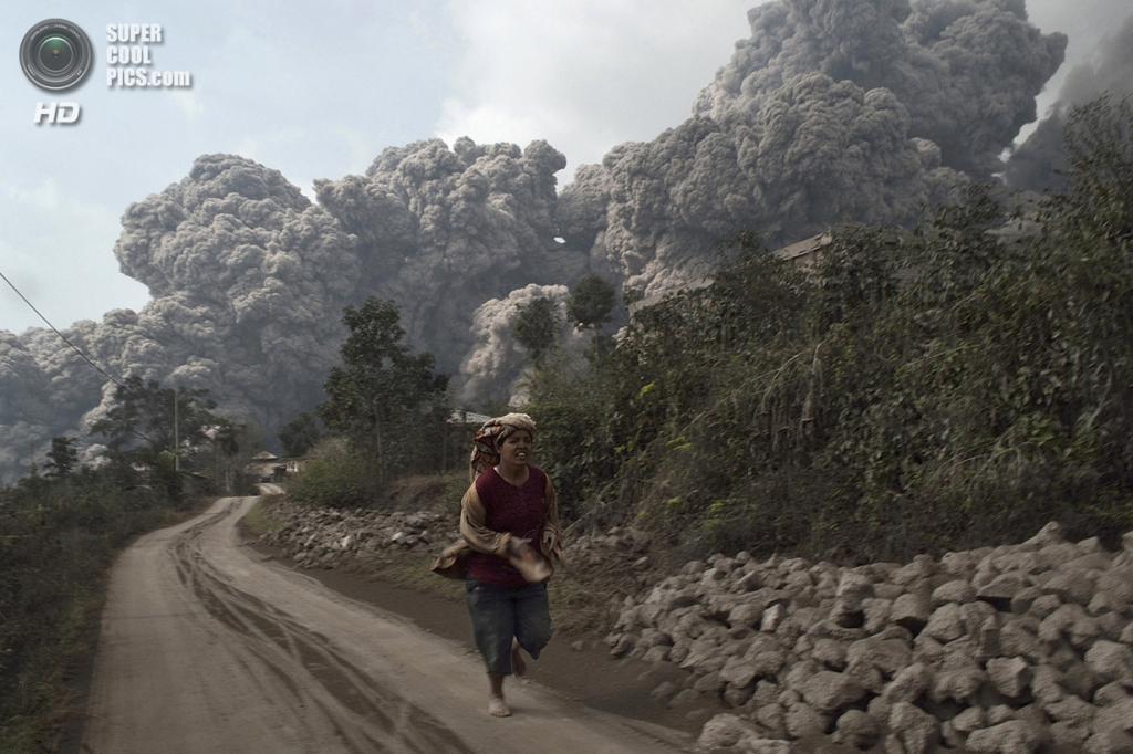 Индонезия. Сигаранг-Гаранг, Северная Суматра. 1 февраля. Женщина убегает от пирокластического потока во время извержения Синабунга. (Reuters/Sutanta Aditya)