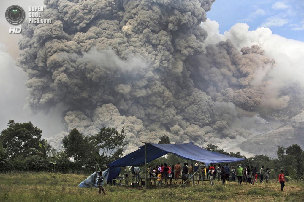 Индонезия. Пертегуан, Северная Суматра. 14 января. Местные жители наблюдают за извержением Синабунга. (AP Photo/Binsar Bakkara)