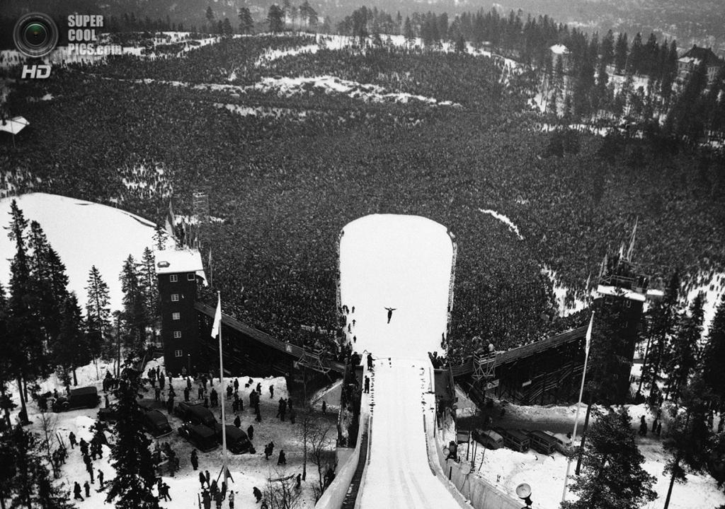 Норвегия. Осло. 24 февраля 1952 года. Тысячи зрителей наблюдают за прыжком Арнфинна Бергманна из Норвегии во время соревнований по прыжкам на лыжах с трамплина. (AP Photo)