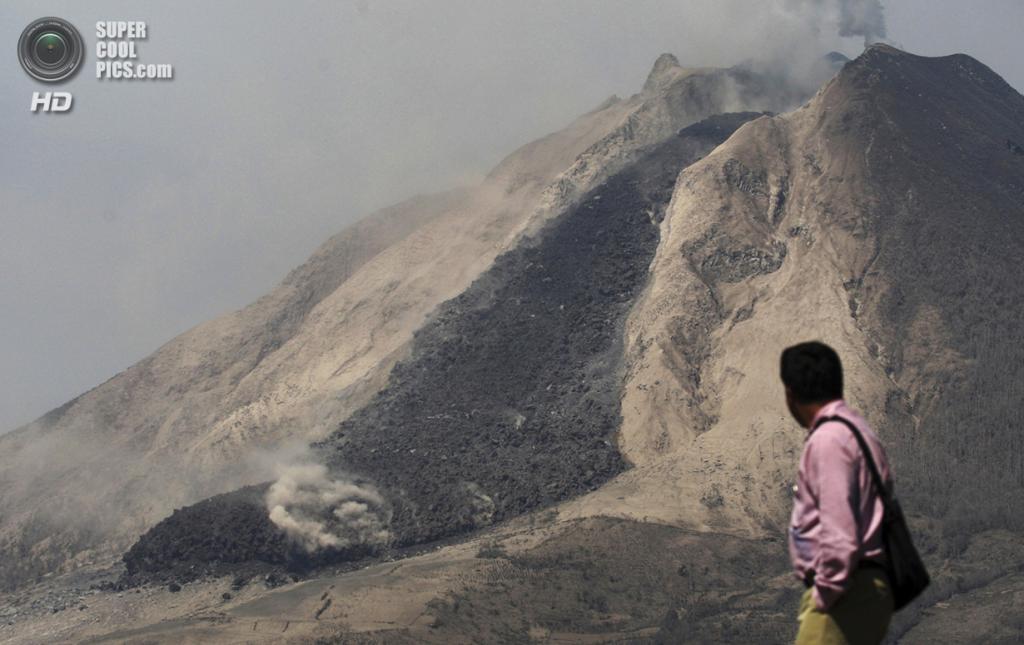 Индонезия. Тига-Кикат, Северная Суматра. 6 февраля. Мужчина наблюдает за извержением Синабунга. (AP Photo/Binsar Bakkara)