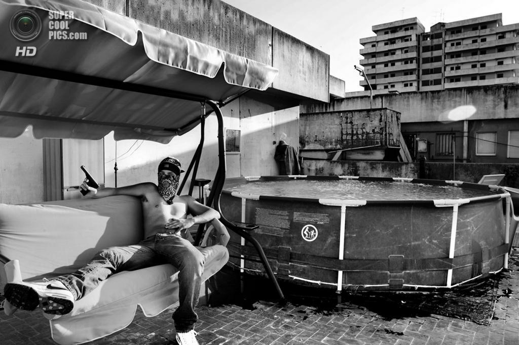 Наркоторговец с пистолетом на крыше здания, известного под названием «Паруса». Скампия — пригород Неаполя, находящийся под контролем Каморры (неаполитанской мафии) — это один из самых больших наркопритонов Европы. Место съёмки: Италия. Неаполь, Кампания. (Esposito Salvatore/2014 Sony World Photography Awards)