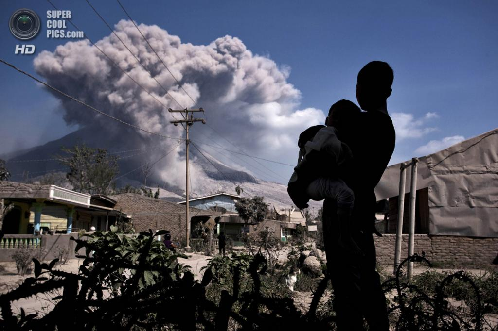 Индонезия. Сибинтун, Северная Суматра. 7 февраля. Парень, держа на руках младшего брата, наблюдает за извержением Синабунга. (Ulet Ifansasti/Getty Images)