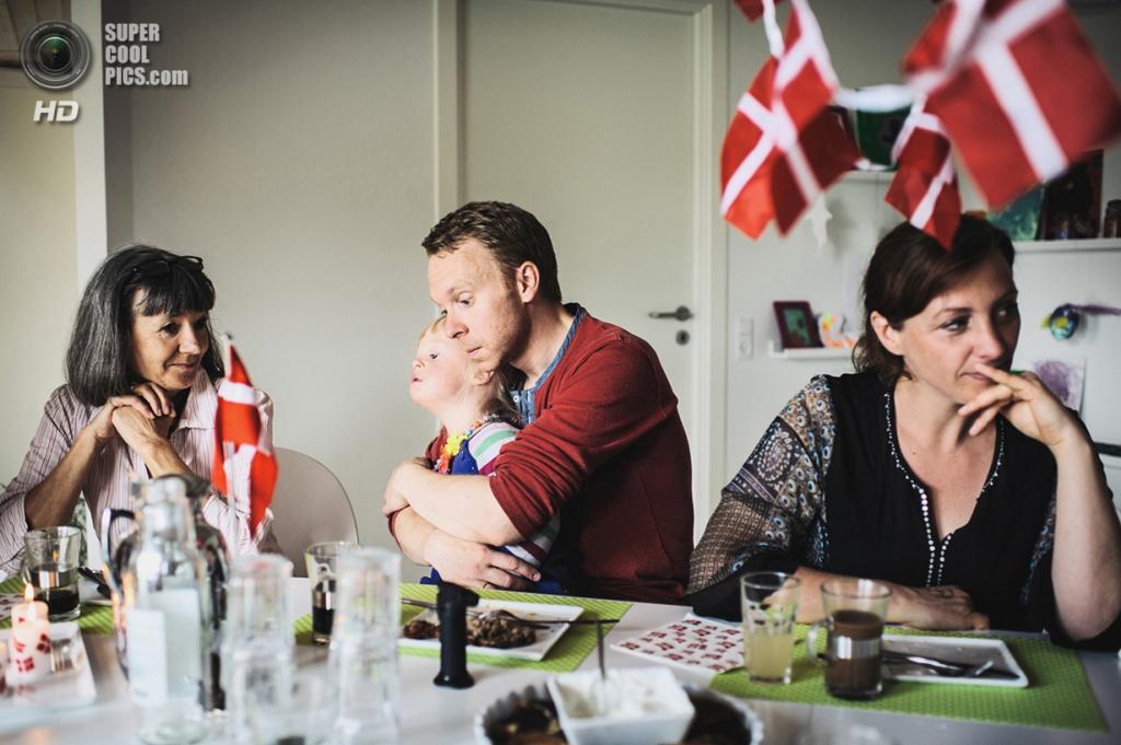5-летняя Эмми с синдромом Дауна. Вместе с родителями, Мартином и Кариной, и младшим братом Кристианом она живёт в деревне близ Орхуса. Вот уже полгода она посещает десткий сад. Её родители были вынуждены в прямом смысле бороться за это право, так как детей с отклонениями в Дании вовсе не жалуют. Эмми в садике хорошо — она быстро учится говорить. Место съёмки: Дания. Орхус. (Mario Wezel/2014 Sony World Photography Awards)