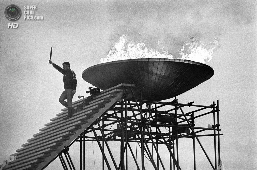 Франция. Гренобль, Изер, Рона — Альпы. 6 февраля 1968 года. Французский фигурист Ален Кальма во время зажжения олимпийского огня на церемонии открытия X Олимпийских зимних игр. (AP Photo)