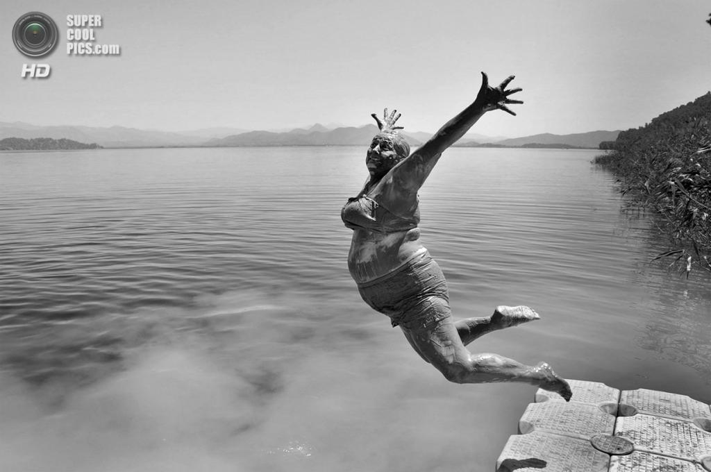 Прыжок в озеро после купания в лечебной грязи. (Alpay Erdem/2014 Sony World Photography Awards)