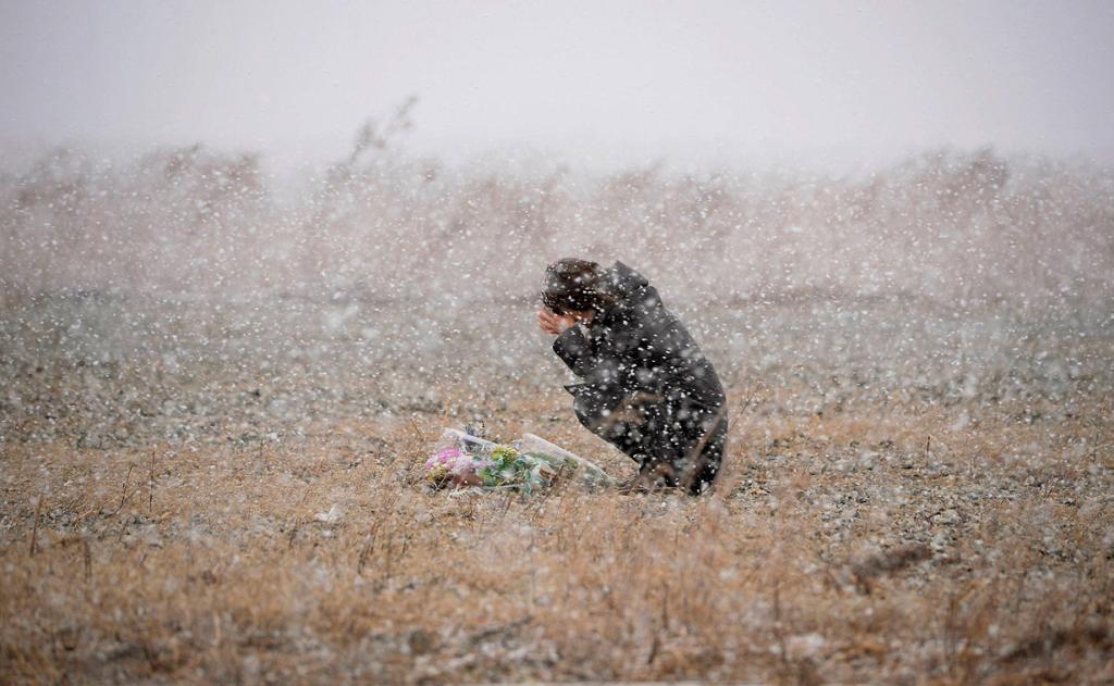 Япония. Рикудзентаката, Иватэ. 11 марта. Женщина молится на том месте, где когда-то была её фотостудия. Город практически полностью разрушен землетрясением и цунами. (REUTERS/Kyodo)