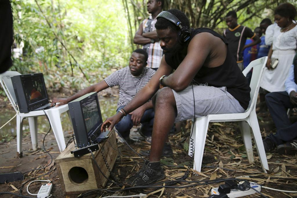 Director Kunle Afolayan watches a monitor while he directs a scene during the filming of police thriller 'October 1' at a rural location in Ilaramokin village