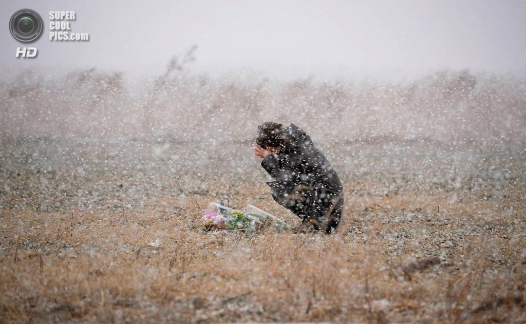 Япония. Рикудзентаката, Иватэ. 11 марта. Женщина молится на том месте, где когда-то была её фотостудия. Город Рикудзентаката был практически полностью разрушен землетрясением и цунами. (REUTERS/Kyodo)