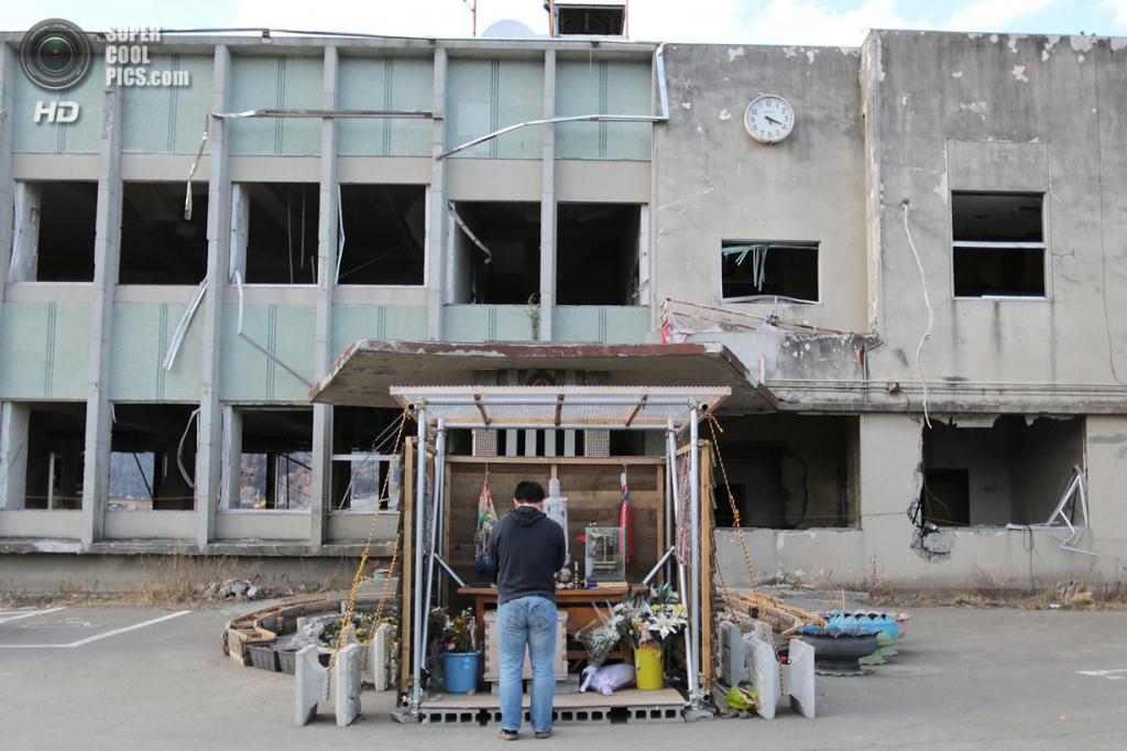 Япония. Оцути, Иватэ. 9 марта. Мужчина молится перед алтарём у разрушенного здания городской администрации. (Yuriko Nakao/Getty Images)