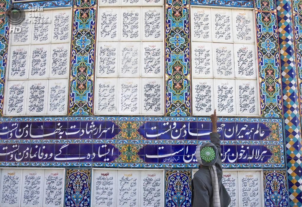 Афганистан. Герат. 5 ноября 2009 года. Работник музея указывает на имена афганцев, которые были убиты в ходе Афганской войны. (REUTERS/Morteza Nikoubazl)