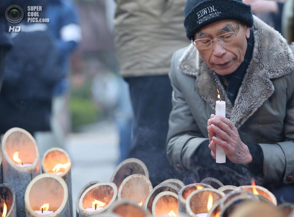 Япония. Кобе, Хёго. 11 марта. Мужчина преклонного возраста молится перед мемориалом «Свет надежды» в память о жертвах землетрясения и цунами 11 марта 2011 года. (Buddhika Weerasinghe/Getty Images)