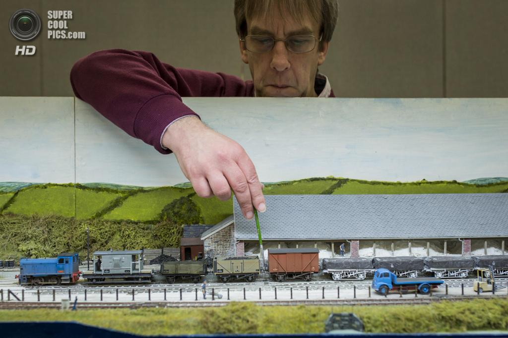 Великобритания. Лондон. 23 марта. Джефф Шеппард настраивает модель железной дороги, которая демонстрирует добычу и перевозку каолинита на юго-востоке Китая. (Rob Stothard/Getty Images)