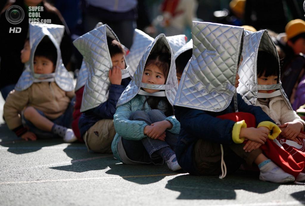 Япония. Токио. 11 марта. Дети сидят на асфальте во время учебной тревоги в детском саду. (REUTERS/Yuya Shino)