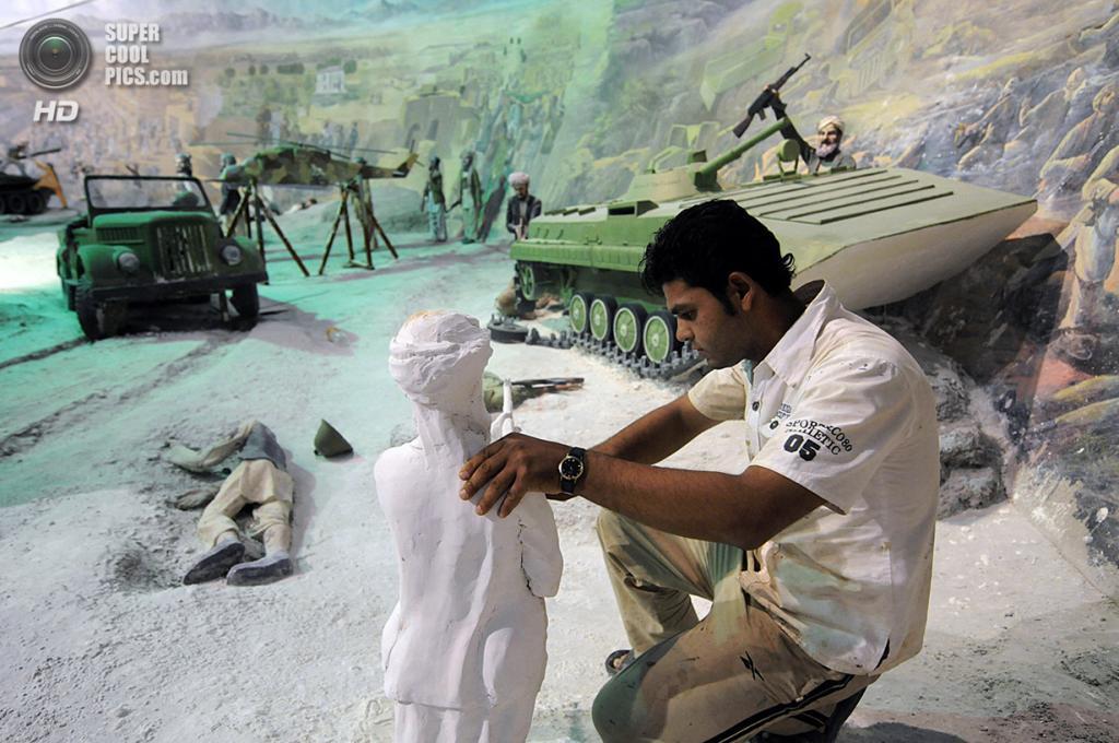 Афганистан. Герат. 8 августа 2009 года. Художник работает над гипсокартонной статуей солдата. (Shah Marai/AFP/Getty Images)