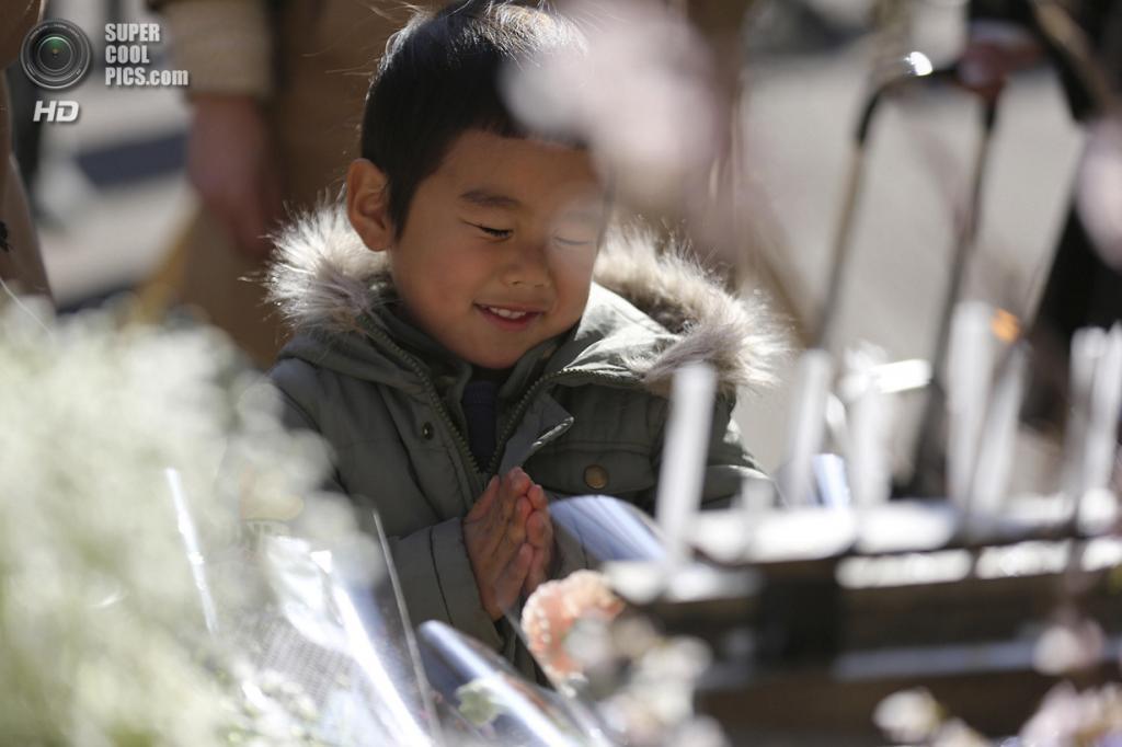 Япония. Токио. 11 марта. Ребёнок молится в память о жертвах землетрясения и цунами 11 марта 2011 года. (AP Photo/Eugene Hoshiko)