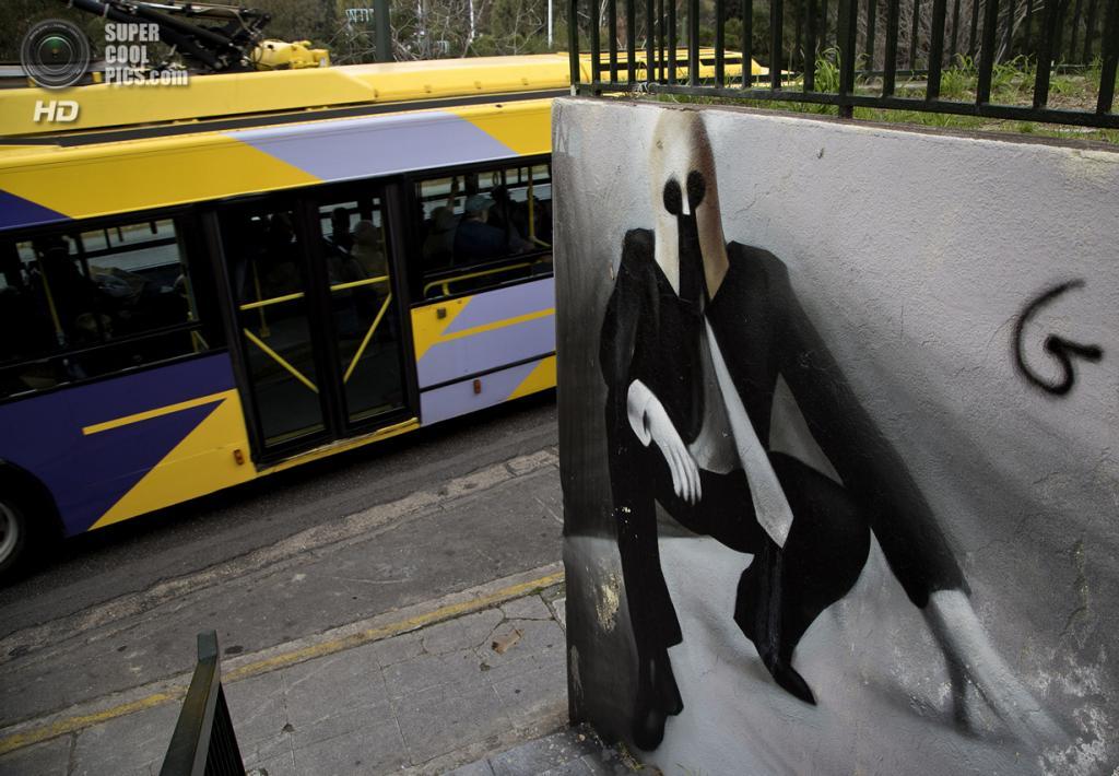 Греция. Афины. 26 февраля. Троллейбус проезжает мимо граффити уличного художника iNO, на котором изображён мужчина в деловом костюме и шлеме спартанца. (AP Photo/Dimitri Messinis)