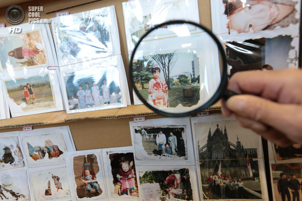 Япония. Сендай, Мияги. 10 марта. Мужчина преклонного возраста использует лупу, чтобы рассмотреть отреставрированные фотографии. (Yuriko Nakao/Getty Images)