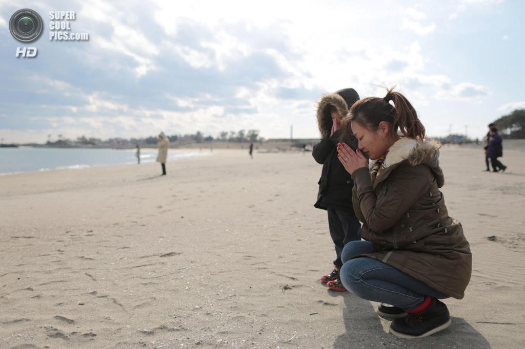 Япония. Ситигахама, Мияги. 11 марта. Юи Гото с сыном во время минуты молчания в 14:46 по местному времени — 11 марта 2011 года в это время цунами нахлынуло на пляж Шобута в Ситигахаме. (Yuriko Nakao/Getty Images)