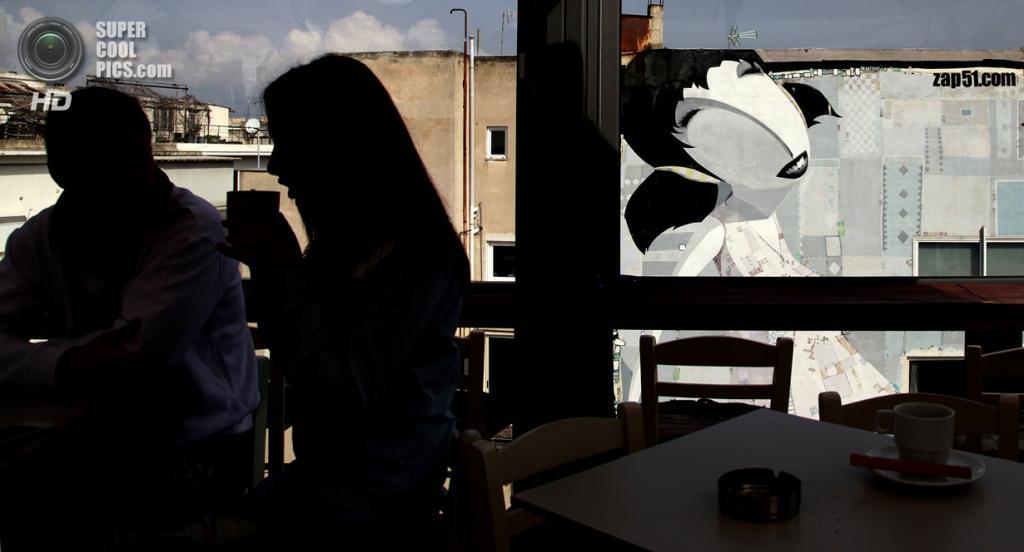 Греция. Афины. 22 февраля. Местные жители пьют кофе в баре напротив граффити уличного художника Zap 51. (AP Photo/Dimitri Messinis)