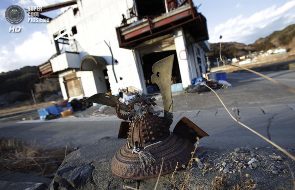 Япония. Оцути, Иватэ. 3 марта. Декоративный шлем самурая, оставленный ржаветь на камнях. (AP Photo/Junji Kurokawa)