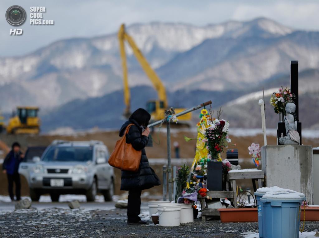 Япония. Исиномаки, Мияги. 10 марта. Женщина молится перед алтарём у главного входа в начальную школу Окава, где пропало без вести множество детей во время землетрясения и цунами 11 марта 2011 года. (AP Photo/Shizuo Kambayashi)