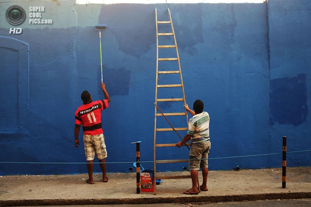 Бразилия. Рио-де-Жанейро. 20 марта. Жители города закрашивают граффити на стене своего дома. (Mario Tama/Getty Images)