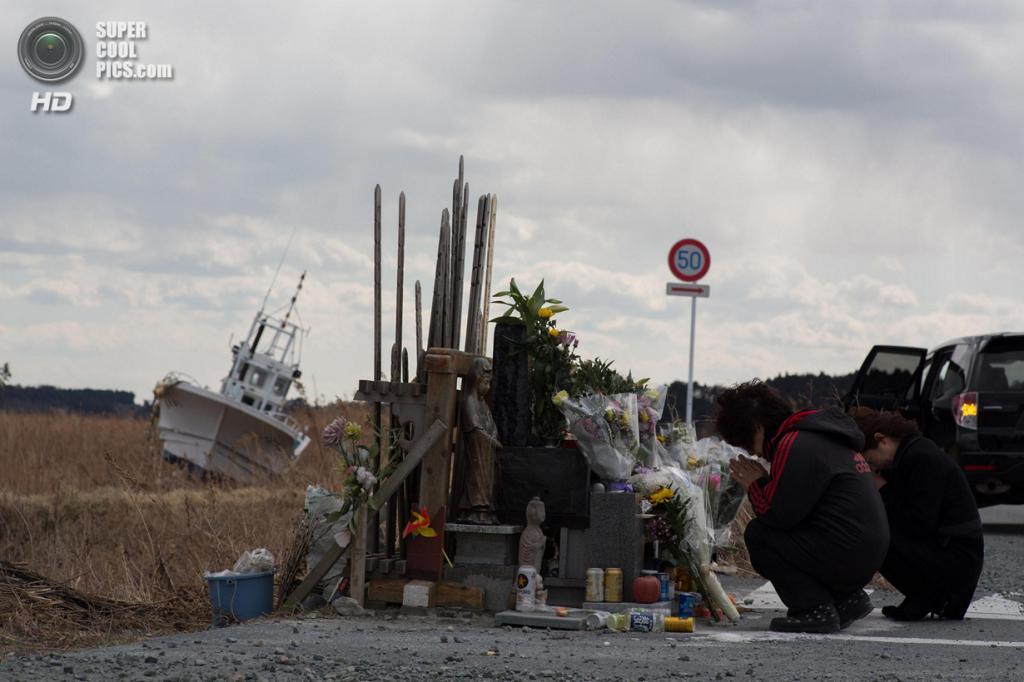 Япония. Укедо, Фукусима. 11 марта. Семья молится перед алтарём в память о жертвах землетрясения и цунами 11 марта 2011 года. (Ken Ishii/Getty Images)