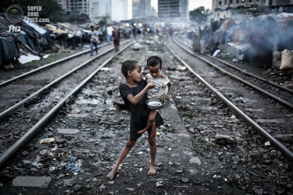 Девочка кормит своего брата в трущобах Кавран, ютящихся вдоль железнодорожных путей. Место съёмки: Дакка, Бангладеш. Номинация: Youth, Environment Category, 1 место. (Turjoy Chowdhury/2014 Sony World Photography Awards)