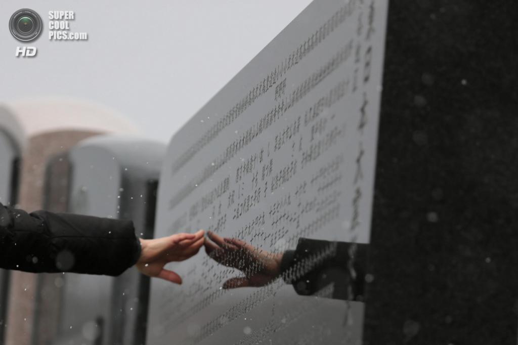 Япония. Исиномаки, Мияги. 11 марта. Женщина касается мемориальной доски с именами жертв землетрясения и цунами 11 марта 2011 года. (Yuriko Nakao/Getty Images)