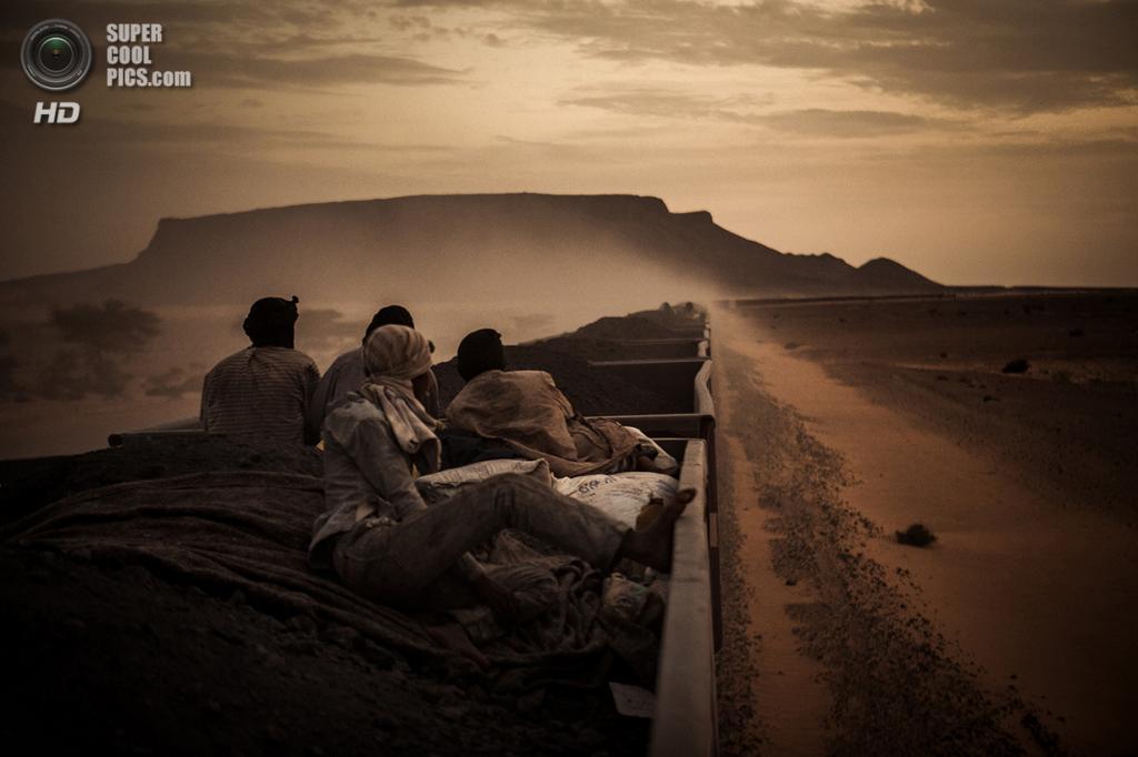 Молодой Мухаммед Салам и его коллеги путешествуют на вагонах с железной рудой из шахтёрского городка Зуэрат посреди Сахары в Нуадибу. Место съёмки: Мавритания. Номинация: National Awards, Испания, 1 место. (Rafael Gutierrez Garitano/2014 Sony World Photography Awards)
