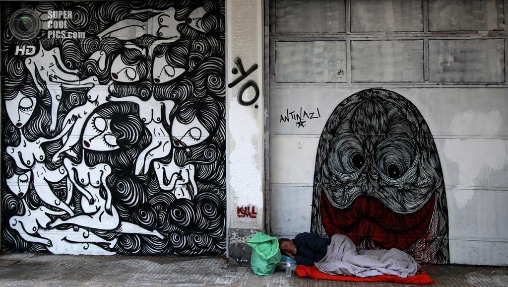 Греция. Афины. 17 февраля. Бездомный спит у граффити уличного художника Sonke. (AP Photo/Dimitri Messinis)