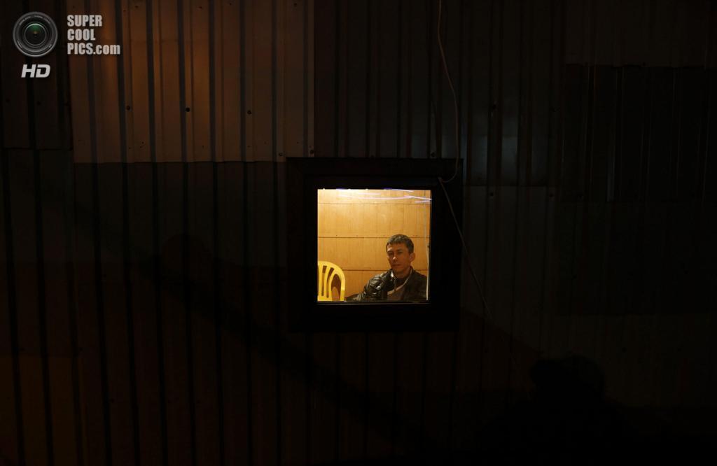 Украина. Симферополь, Крым. 9 марта. Часовой у окна. (REUTERS/Vasily Fedosenko)