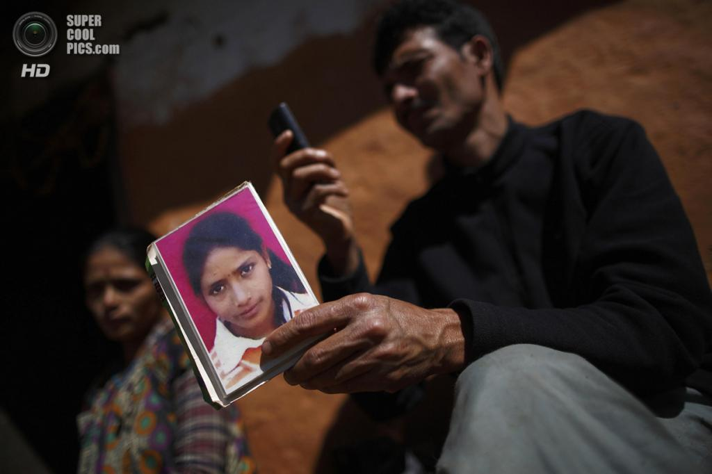 Непал. Ачхам, Западный регион. 17 февраля. Отец Самилы Бхул с портретом погибшей дочери. (REUTERS/Navesh Chitrakar)