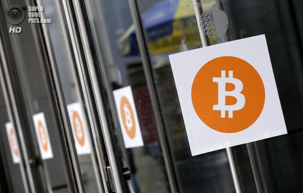 США. Нью-Йорк. 7 апреля. Логотипы Bitcoin на дверях «Джавитс-центра». (AP Photo/Mark Lennihan)