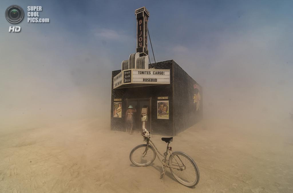 Песок кружится вокруг участников фестиваля Burning Man, заглядывающих в двери театра «Блэк-Рок-Бижу». (Mark Kaplan/Smithsonian.com)