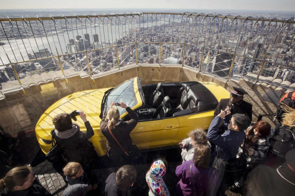 Tourists look at new 2015 Ford Mustang GT on the observation deck of Empire State Building in New York