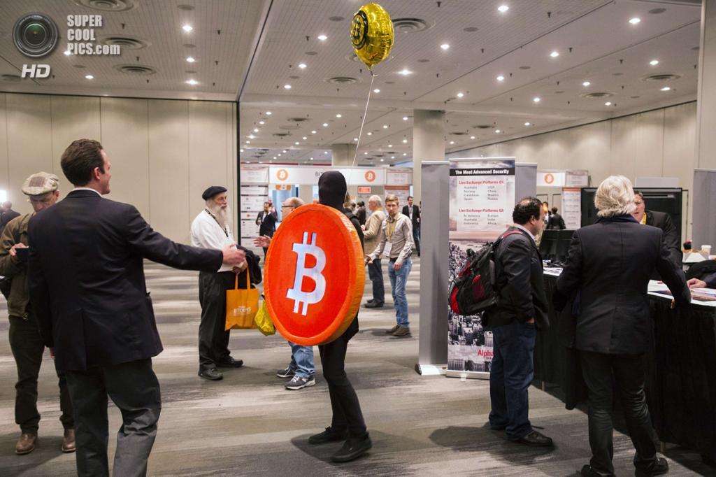США. Нью-Йорк. 8 апреля. Человек в костюме монеты приветствует посетителей и участников конференции. (REUTERS/Lucas Jackson)