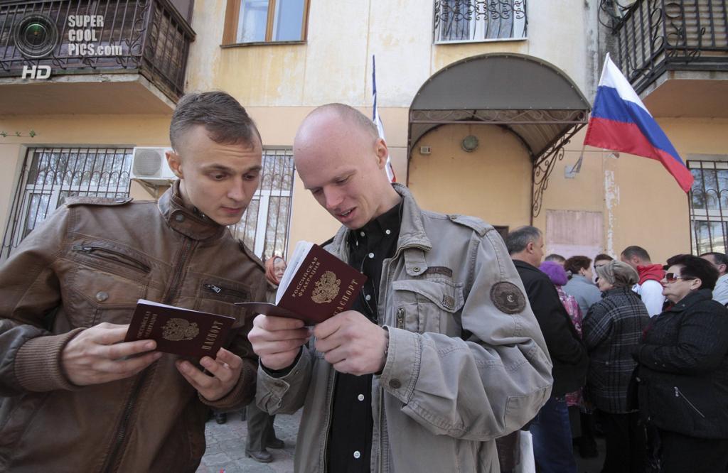 Крым. Симферополь. 3 апреля. Местные жители рассматривают свои новые российские паспорта. (REUTERS/Stringer)