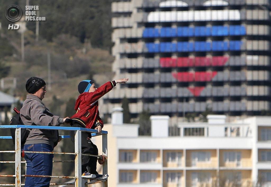 Крым. Алушта. 8 апреля. Мальчик бросает камни в воду на фоне гостиницы с сердцем, стилизованным под флаг РФ. (REUTERS/Maxim Shemetov)