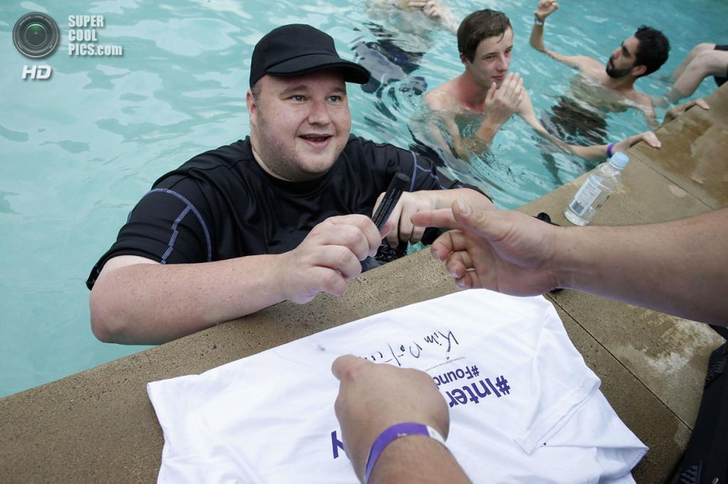 Новая Зеландия. Коутсвилл, Окленд. 13 апреля. Ким Дотком подписывает футболки с логотипом Интернет-партии Новой Зеландии. (REUTERS/Nigel Marple)