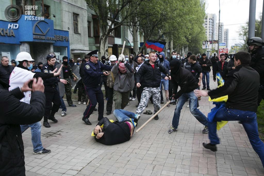 Украина. Донецк. 28 апреля. Пророссийские активисты атакуют мужчину с украинским флагом. Милиционеры не слишком им в этом мешают. (REUTERS/Baz Ratner)