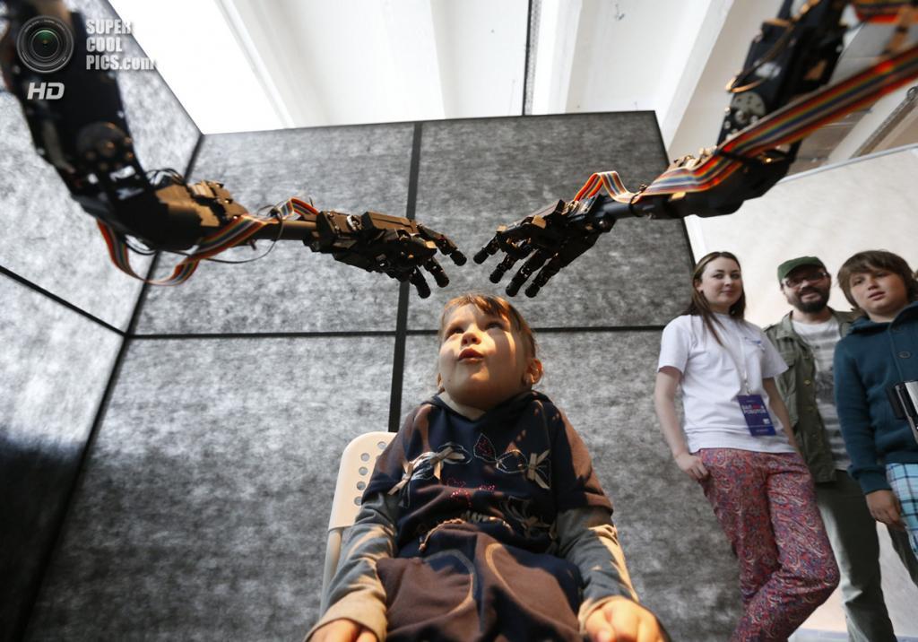 Россия. Москва. 17 мая. Девочка сидит в кресле перед роботом The Blind Robot из Сингапура. (REUTERS/Sergei Karpukhin)