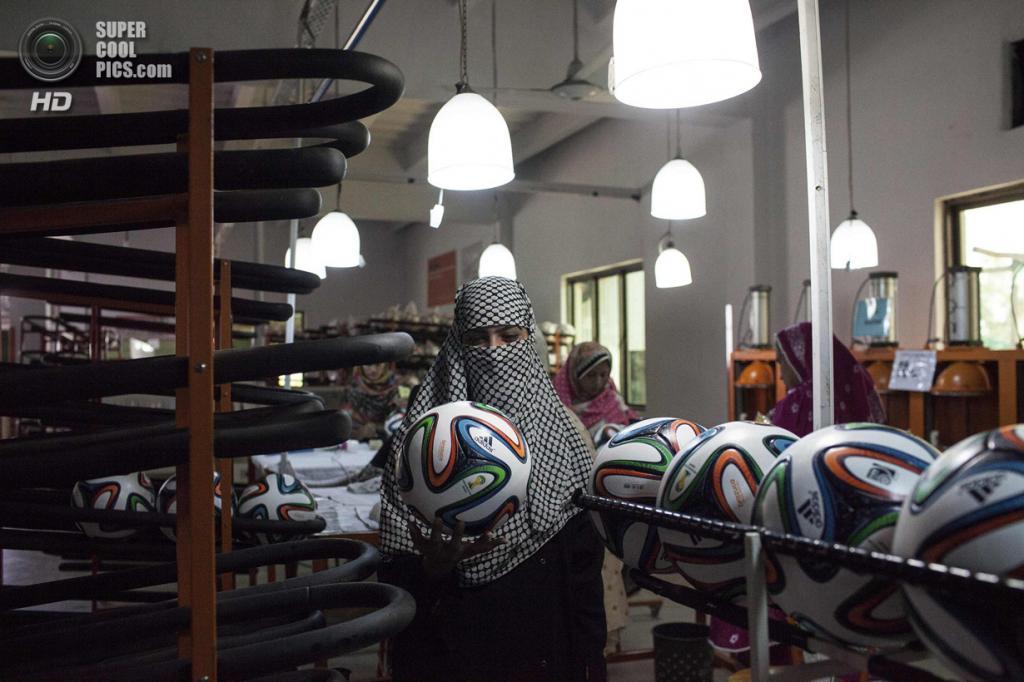 Пакистан. Сиялкот, Пенджаб. 16 мая. Работница фабрики по производству футбольных мячей проверяет форму продукции. (REUTERS/Sara Farid)