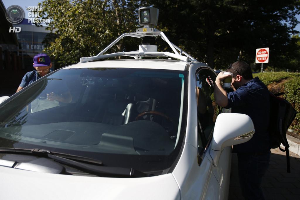 США. Маунтин-Вью, Калифорния. 13 мая. Журналисты разглядывают салон беспилотного автомобиля Google. (REUTERS/Stephen Lam)