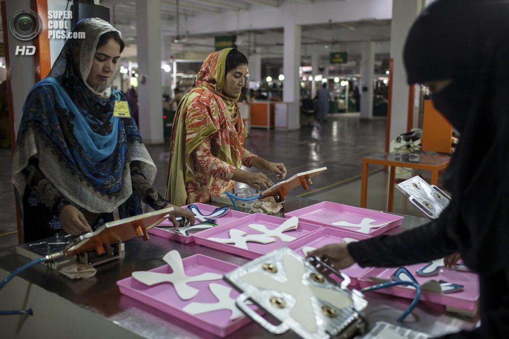 Пакистан. Сиялкот, Пенджаб. 16 мая. Работницы фабрики производят фигурные панели для оклейки мячей. (REUTERS/Sara Farid)