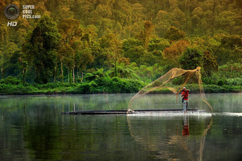 45-летний рыбак по имени Дадин. Он использует традиционную сеть для ловли рыбы в озере. (Ricky Martin/CIFOR)